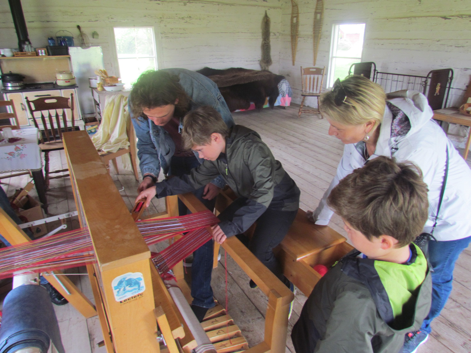 visitors from france try the four petal loom